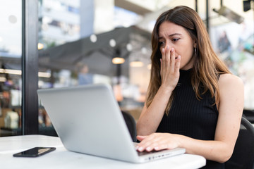 Business woman work process concept. Shocked female freelancer stares at laptop computer with bugged eyes, Blurred background, film effect. Wall mural