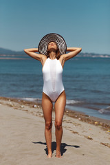 Young woman posing on the beach in a white swimsuit and hat