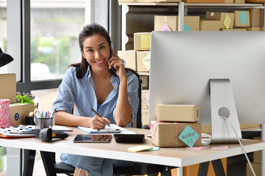 Young Asian woman entrepreneur/ Business owner working with computer at home