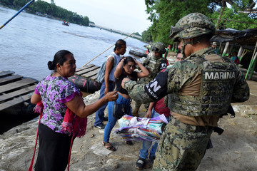 A member of the naval police checks the ID of a Guatemalan woman that crossed the Suchiate river on a raft from Tecun Uman, in Guatemala, to Ciudad Hidalgo