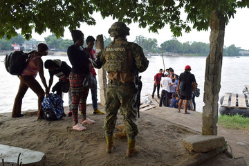 A member of the naval police checks the ID of people that crossed the Suchiate river on a raft from Tecun Uman, in Guatemala, to Ciudad Hidalgo