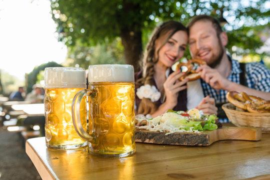 Bier Maßkrüge, Paar sitzt im Biergarten mit Brotzeit im Hintergrund