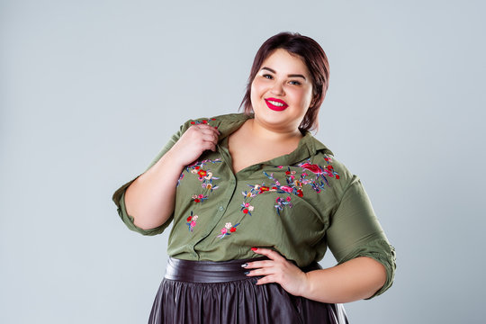 Plus size fashion model in casual clothes, fat woman on gray background