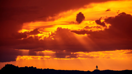 Silhouette Of Man Standing On Mountain Desert Ridge In Arches National Park Under Spectacular Sunset Clouds and Sun Rays