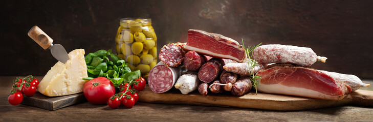 Fototapeta Italian food. Various kind types of salami, speck, sausages, parmesan cheese, olives, basil and fresh tomatoes