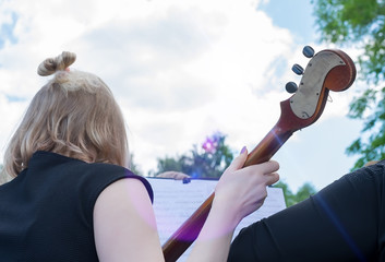 Girl at a street concert outdoors playing the contrabass, a musical instrument, looking at a...