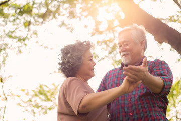 Old woman or wife dancing with old man or husband at park under tree in morning. Grandmother and grandfather feel happiness at the wonderful moment time with smiley faces. Senior couple is romantic