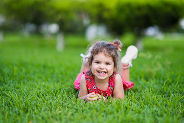 Happy Smiling Little Toddler Girl Laying On Grass In Park With Red Dress
