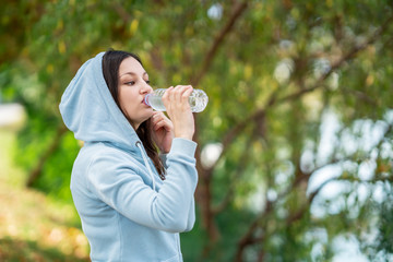 Thirsty woman drinking water after sport activities.Health concept.