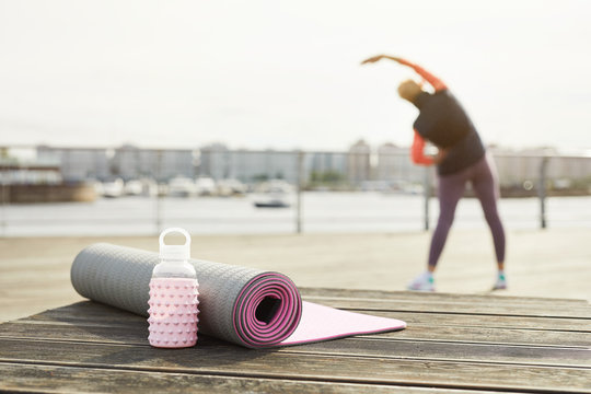 Back view of unrecognizable woman stretching on wooden pier outdoors with focus on yoga mat in foreground, copy space