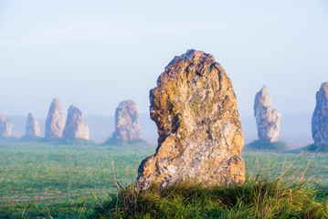 Menhir alignment view at Camaret sur mer at sunrise during fog. France