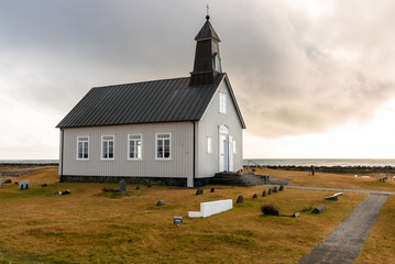 Lonely chapel onthe coast of Iceland at sunset in autumn Wall mural