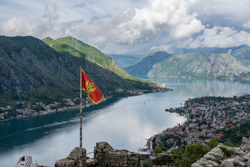 Aerial view of Dobrota and Kotor from hike to Fortress with Montenegro national flag