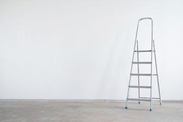 Ladder on a white wall background with copy space. Under construction concept background.