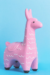 Poster Lama Pink zine type toy lama on a blue background close up, coin bank. Creative and fun trendy collage of funky animal concept with copy space