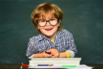Back to school and happy time. Funny little boy in glasses on blackboard background. Kid with a...