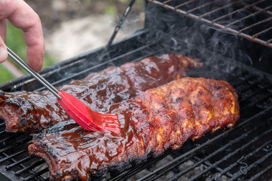 Pork ribs cooking on barbecue grill for summer outdoor party.
