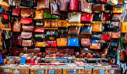 Colorful leather purses, handbags, wallets and handbags are displayed by street vendors at an outdoor Market, in Florence, Italy.