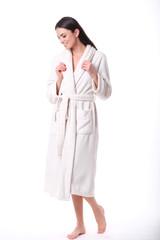 Studio shoot of model in white bathrobe looking down.