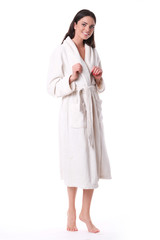 Model in white bathrobe standing at the white background.