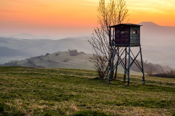 Papiers peints Chasse Beautiful mountain colorful landscape. Hunting pulpit and the setting sun over the hills.