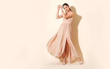 Beautiful model dancing in long elegant dress.