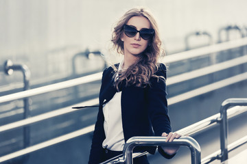 Young fashion blonde business woman in sunglasses leaning on railing