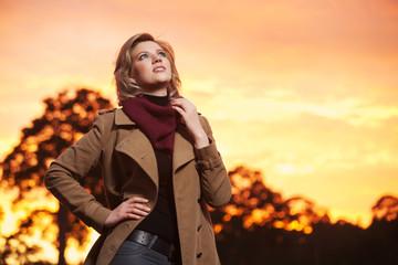 Young fashion woman in beige coat walking outdoor