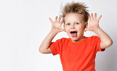 Grimacing kid boy in orange t-shirt shows big ears with his hands and put his tongue at us
