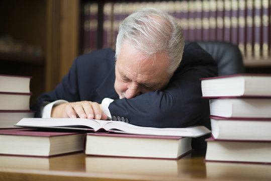 Bored businessman sleeping on books in his office
