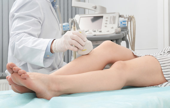 Doctor conducting ultrasound examination of patient's knee in clinic, closeup