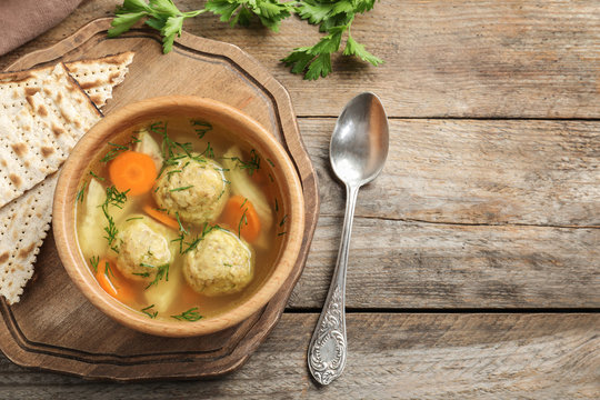 Flat lay composition with Jewish matzoh balls soup on wooden table. Space for text