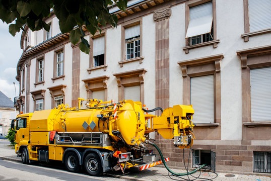 Side view of powerful professional modern yellow sewage sewerage truck working near a house pumping basement canalisation water