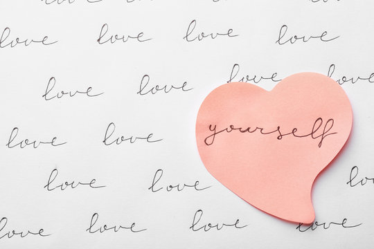 Composition with words LOVE YOURSELF and paper heart on white background, top view