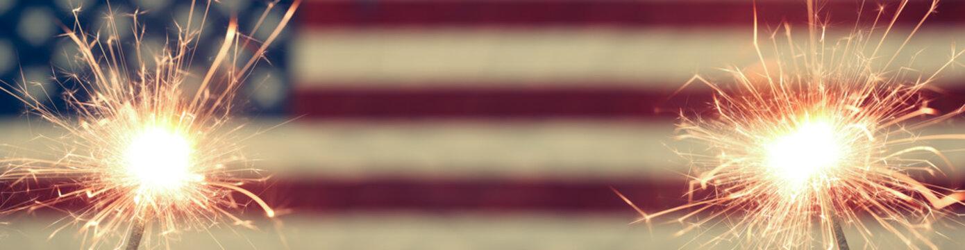 Lit sparkler burning in front of American Flag