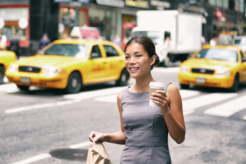 New York Asian business woman walking to work with lunch bag in the morning commuting drinking...