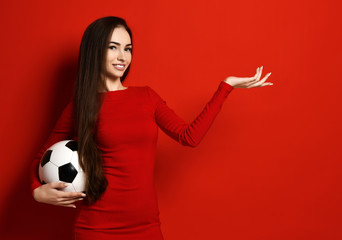 Pretty smiling brunette woman in tight red dress holds soccer ball in one hand and  showing open palm hand for free text space