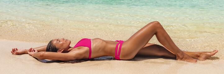 Suntan beach bikini woman lying down on sand relaxing sunbathing panoramic banner. Summer travel lifestyle swimsuit model tanning with sun tanned skin.