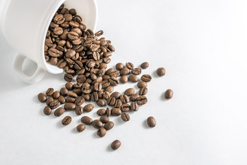 Scattered coffee beans from a cup on a white background. Pile of brown roasted coffee beans in coffee cup. Concept of freshness or great aroma and energy .