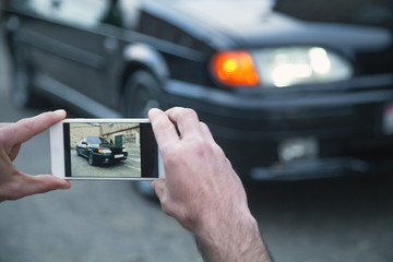 Man taking photo of a car on his phone.