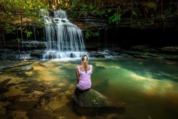 Fotobehang - Woman enjoying nature. Dappled sunlight at the waterfall rock pool