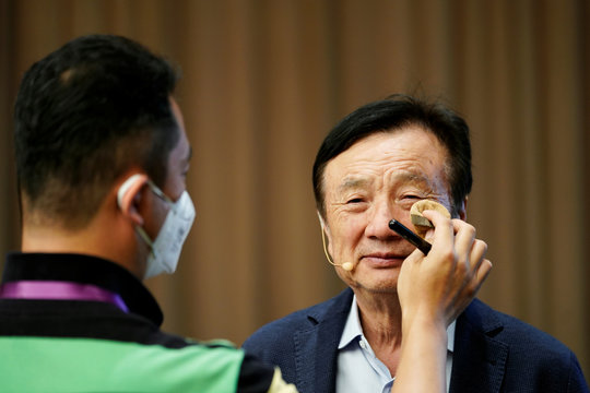 Staff member applies makeup for Huawei founder Ren Zhengfei before a panel discussion at the company headquarters in Shenzhen