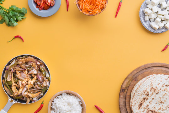 Fajitas and ingredients top view and yellow background