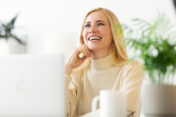 Happy Mature Woman Dreaming when Websurfing On Laptop