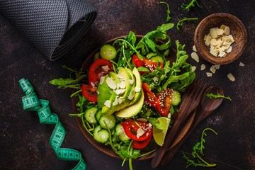 Green salad with avocado, tomatoes, cucumbers and nuts in wooden plate, centimeter on dark background. Fitness and diet food concept.