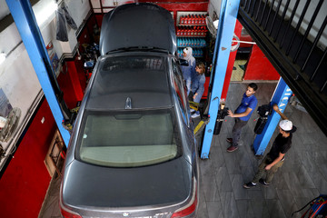 Jordanian female mechanics Ahlam al Atayyar and Hiba al Juqa check the car of one of their clients in Amman