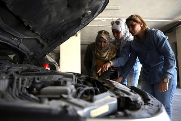Jordanian female mechanics, Ahlam al Atayyar and Hiba al Juqa, check the car of one of their clients in Amman