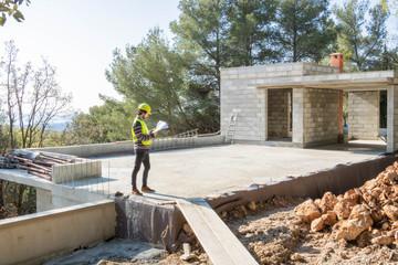 Apprenti artisan, métier du bâtiment vérifiant un plan sur un chantier de maison en construction