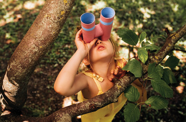 Little girl looking through a binoculars searching for an imagination or exploration in summer day...