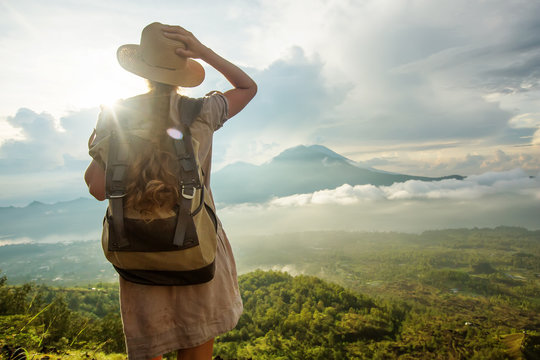 Woman enjoying sunrise from a top of mountain Batur, Bali, Indonesia.